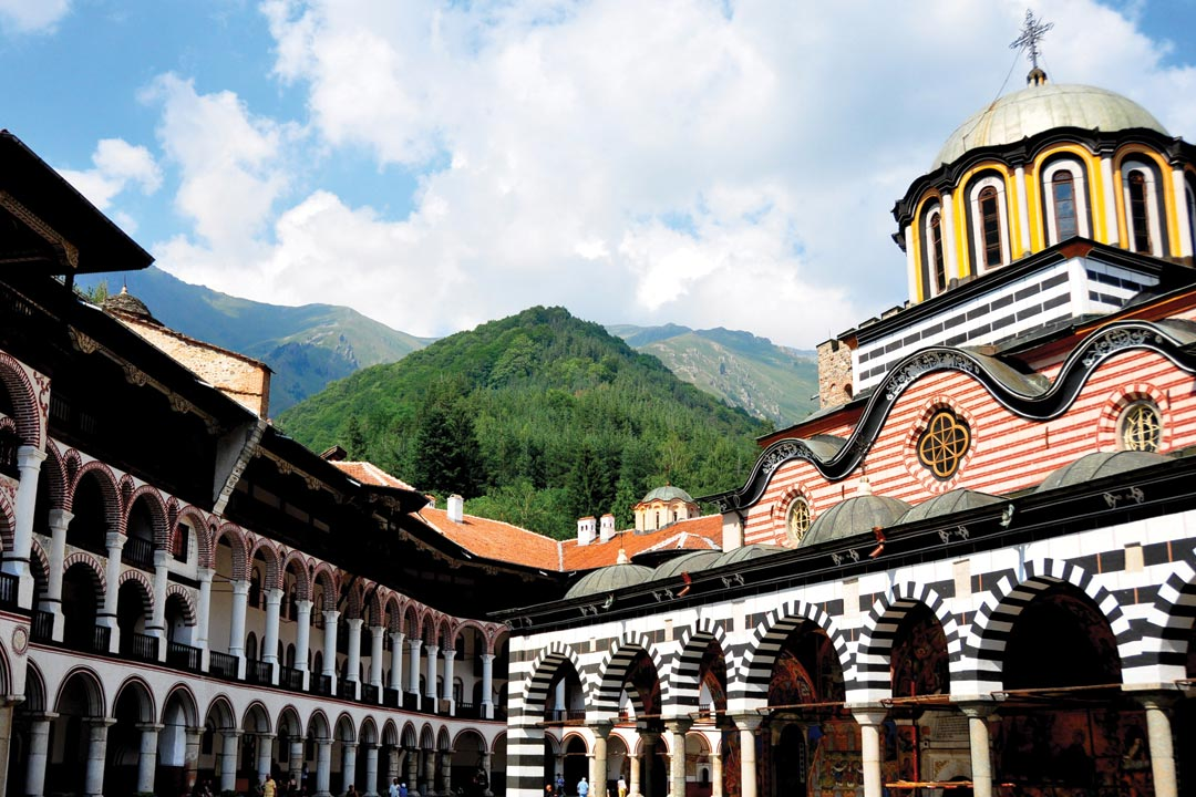 Orthodox Monastary in the mountains with white and black arch cloisters