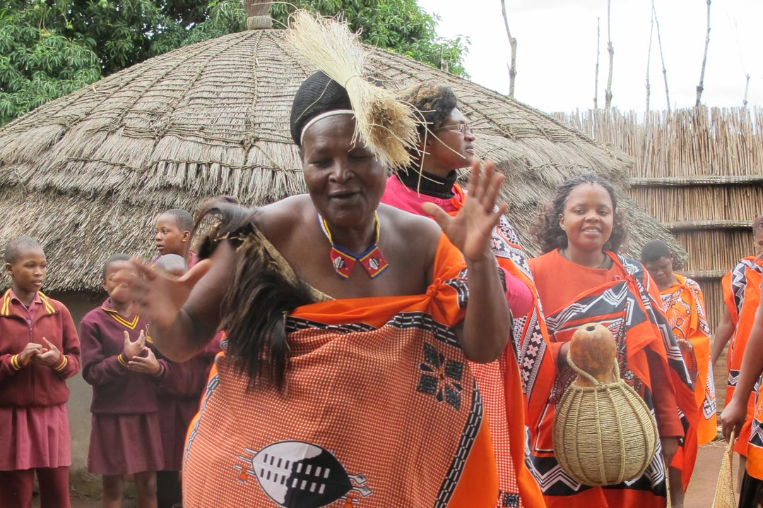 A Swazi Lady in orange robes showing us her dance moves in a Swazi Village