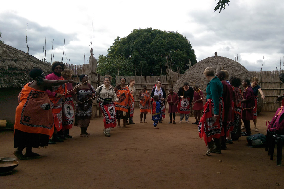 Traveleyes travellers wearing robes dancing with local Swazi village women