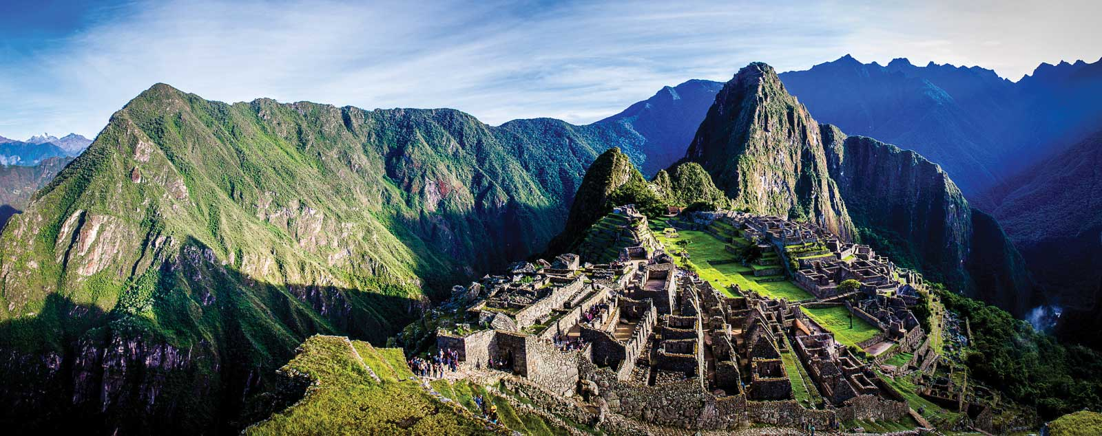 The ruins of Machu Picchu high in the green Andes Mountains under a bright blue sky.