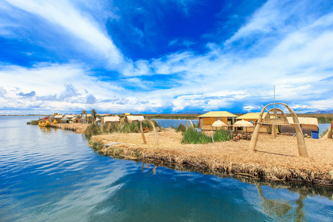 The man-made Uros Reed Islands under a bright blue sky.