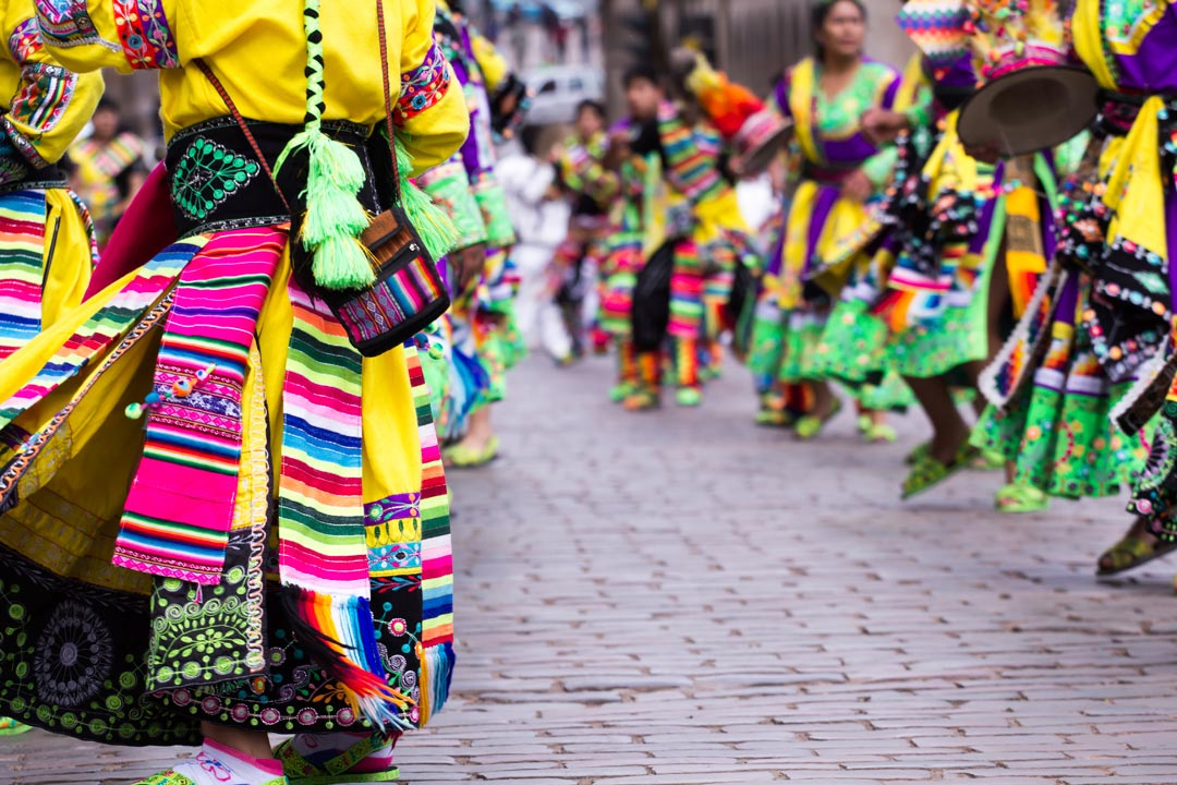 Peruvians dressed in bright yellows, pinks and purples dancing and singing on a cobbled road.