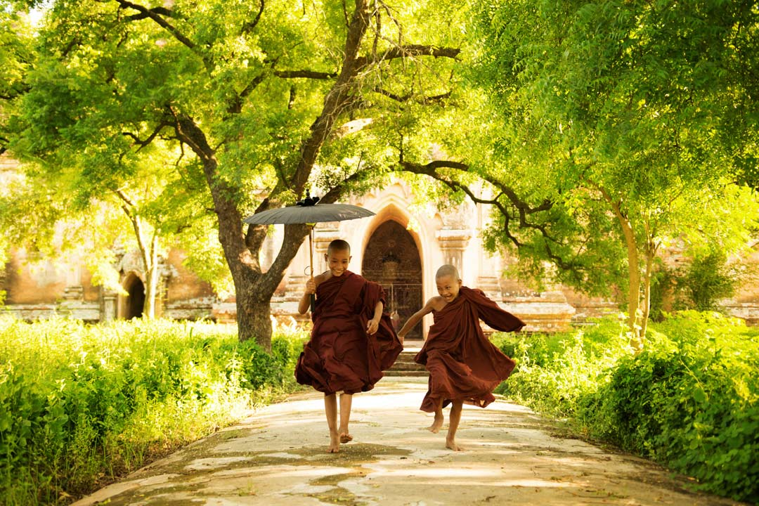 Two Burmese monk children running from a temple in the sunshine.