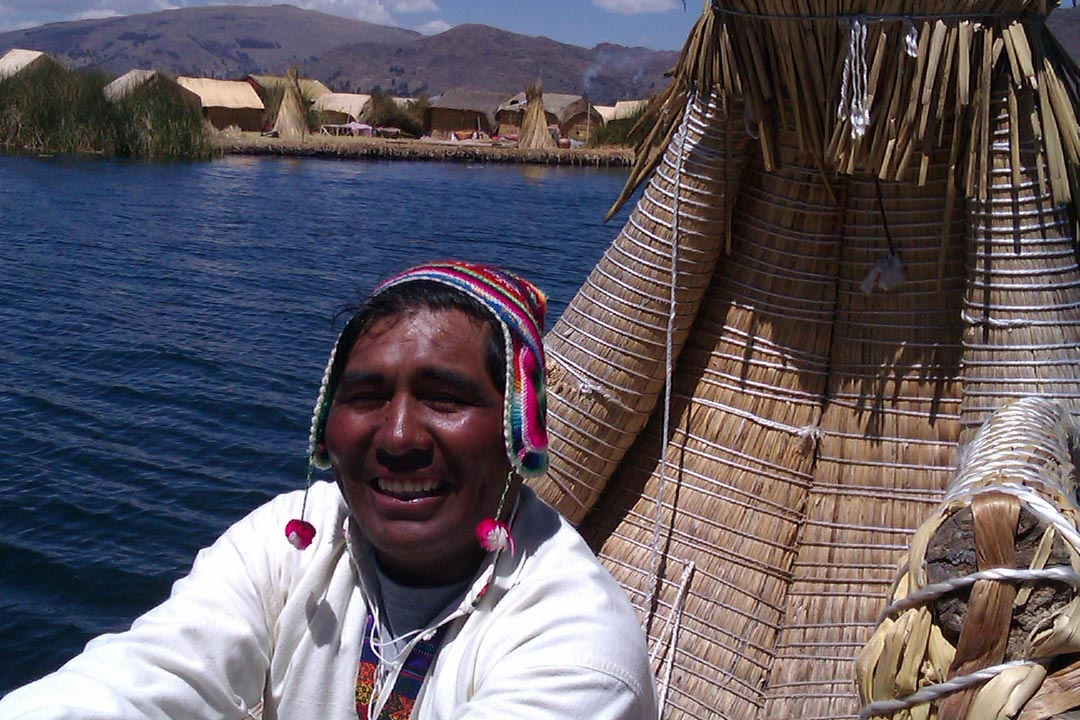 A Peruvian man in a colourful hat sailing a boat made of reeds in the Uros Islands.