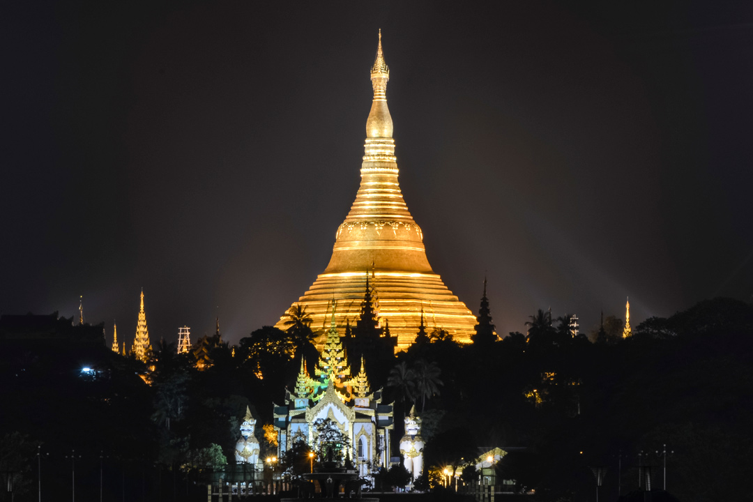 The golden Schwedagon Pagoda towering into the night sky gleaming in spotlights.
