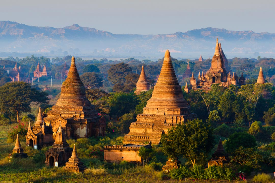 The towering temples of Bagan surrounded by greenery and a sunny haze.