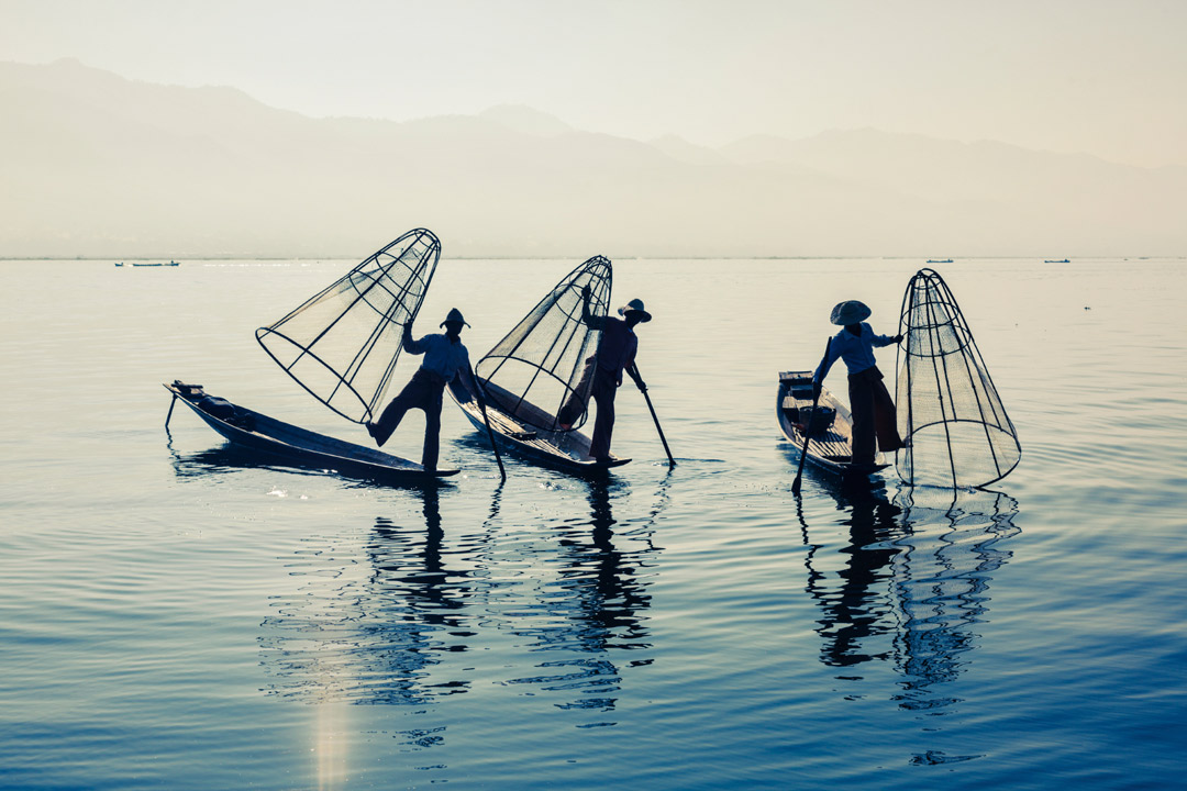 Three Burmese fishermen rowing the traditional way with their legs on a clear blue lake.