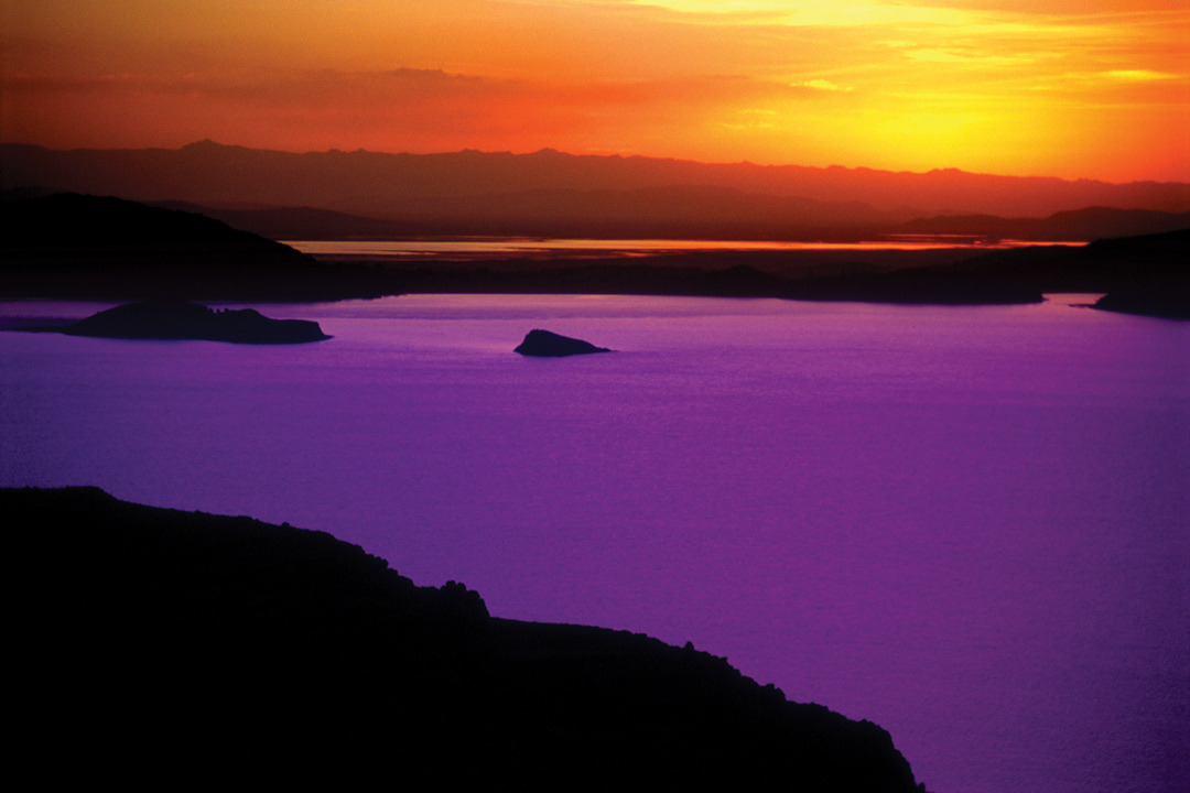 The sun setting over a lake creating a purple sheen on the water.