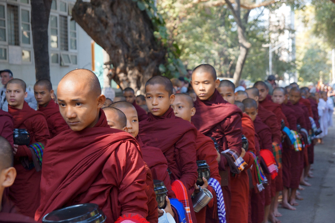 A line of Buddhist monks robed in red collecting alms.