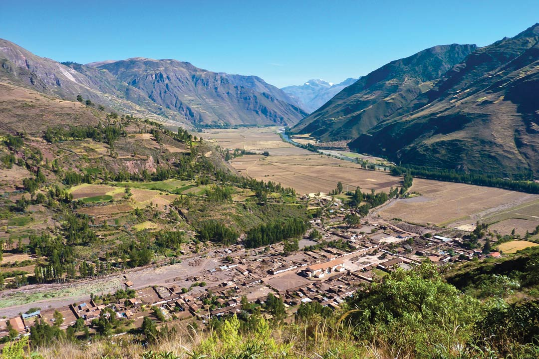 A green and brown valley in the Andes Mountains.