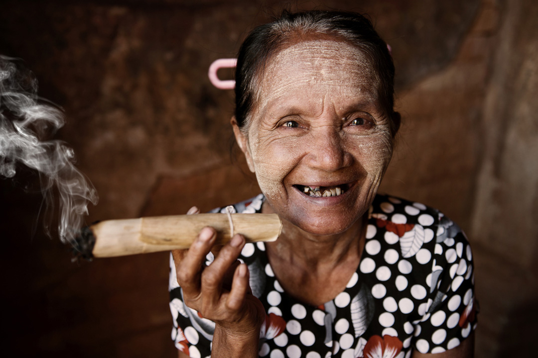 A Burmese woman with Thanaka paste on her face smoking a hand-rolled cigar.