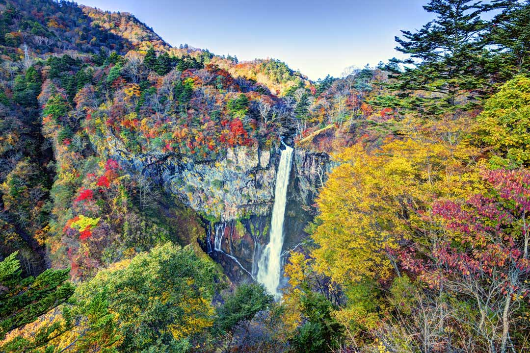 A waterfall cascades down a cliff surrounded by vibrant autumnal coloured trees