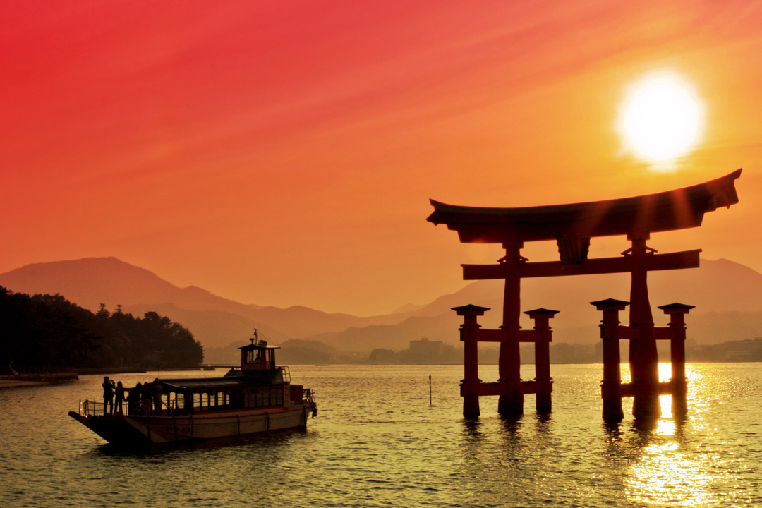 A orange sun sets over a Lake with a Japanese Gate sitting in the water by a boat.