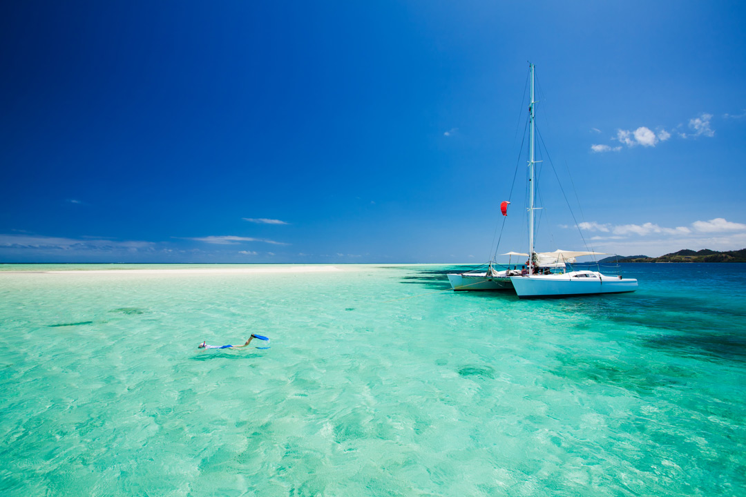 A catamaran yacht is anchored in clear blue oceans, while a snorkeler is exploring the underwater paradise