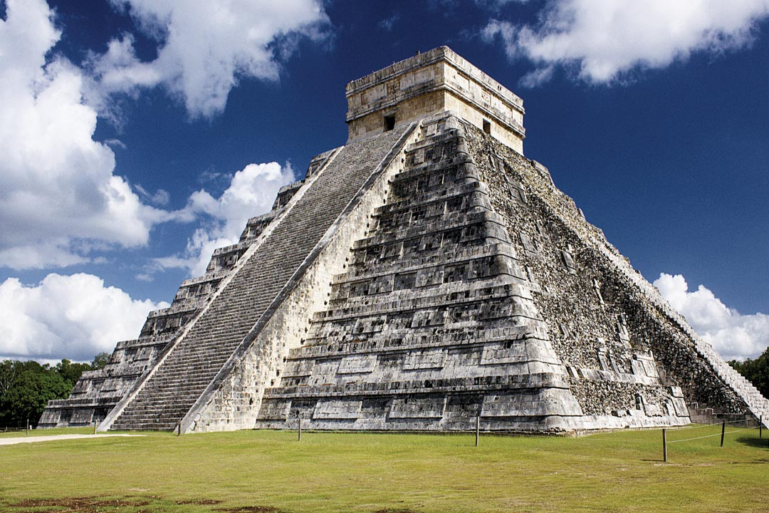 A looming pyramid known as El Castillo or the Temple of Kukulcan, stands out against a bright blue sky. This Mesoamerican step-pyramid dominates the center of the Chichen Itza archaeological site