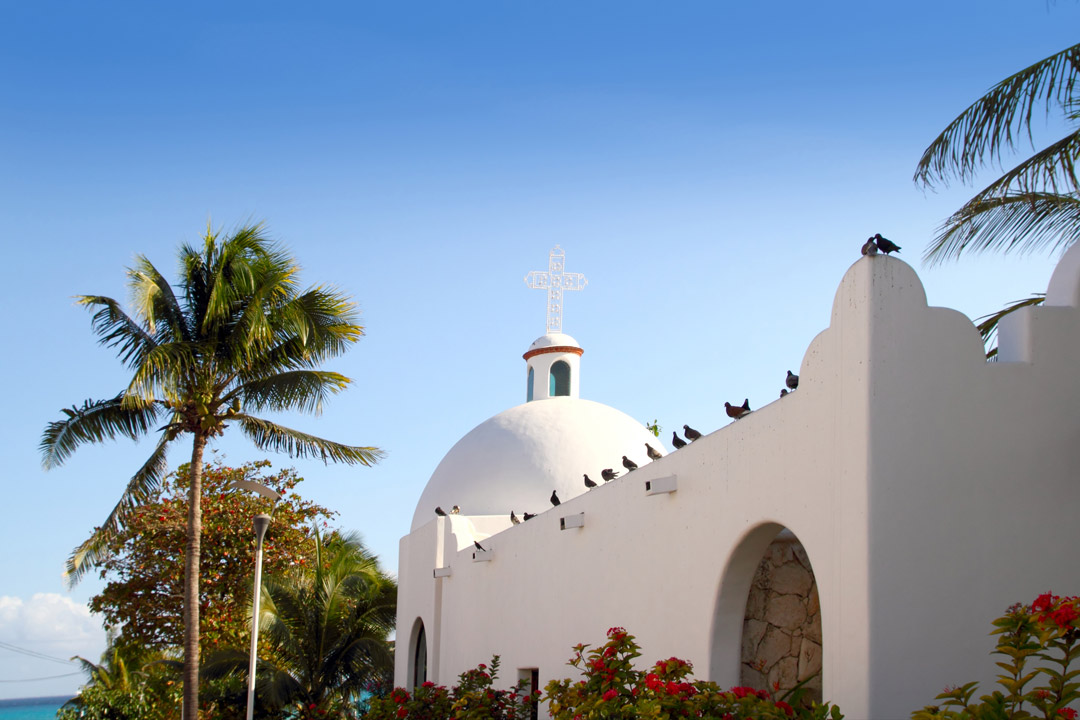 Birds sitting on a pristine white church which is surrounded by palm trees and tropical plants
