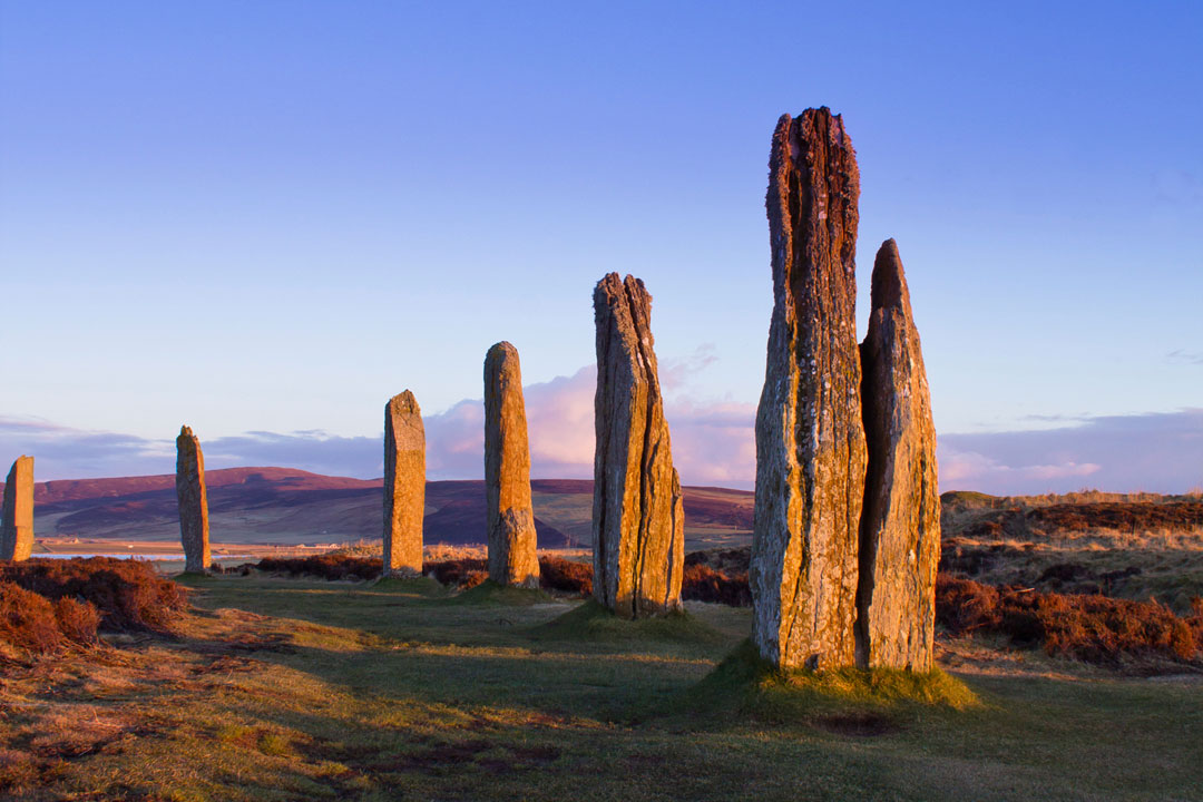 An ancient henge of standing stone pillars in a row at twilight in the Orkneys