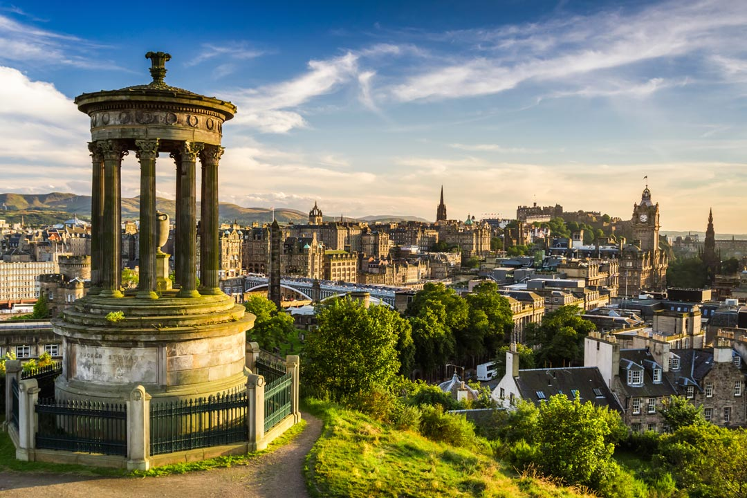 Panoramic image of the historic buildings and ornaments of Edinburgh under a clear blue sky