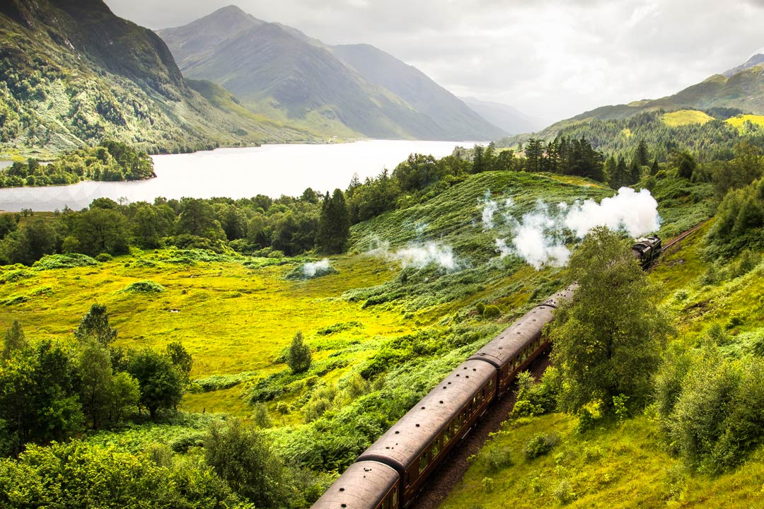A steam locomotive with a plume of smoke journeying through lush green highland countryside with a lake in the background