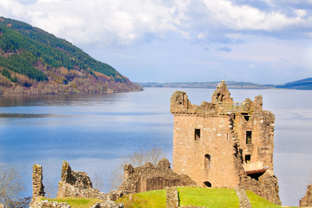 Viewing the calm blue waters of Loch Ness with the ruins of Urqhart Castle in the foreground