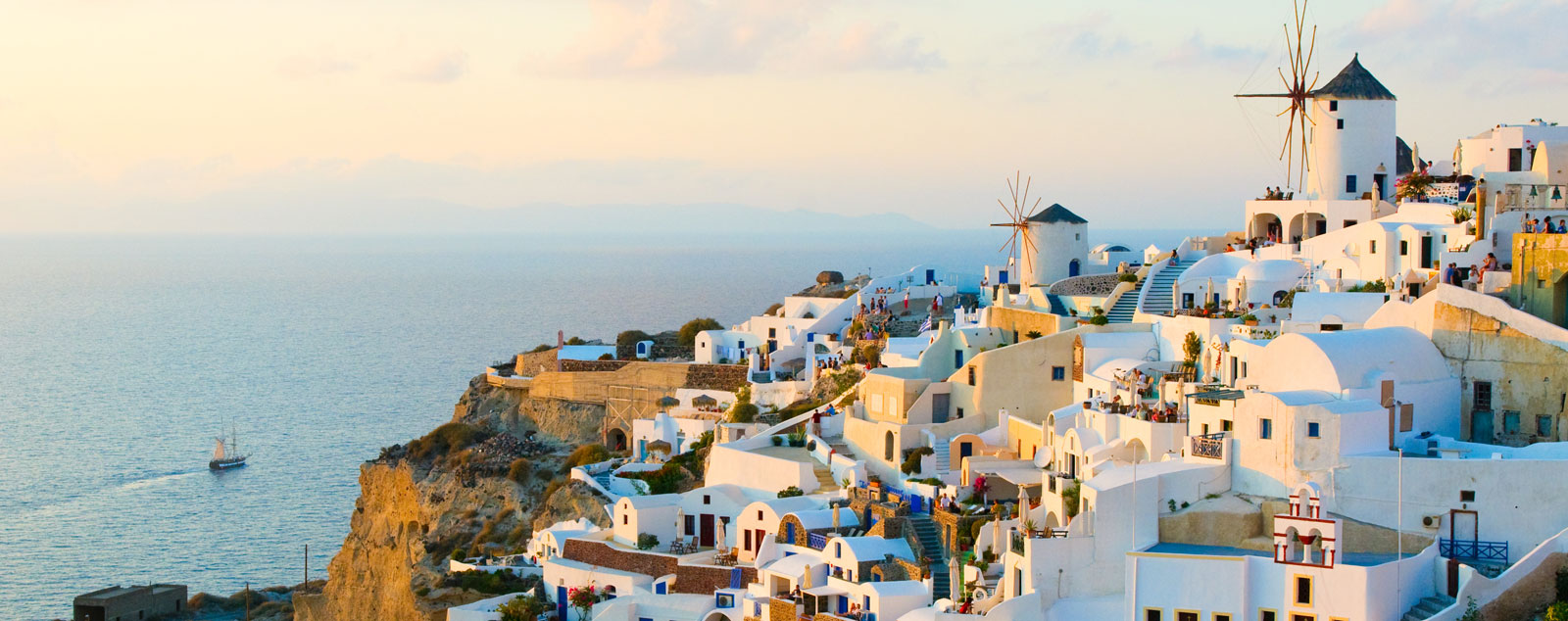 Whitewashed houses and windmills of Santorini atop a cliff
