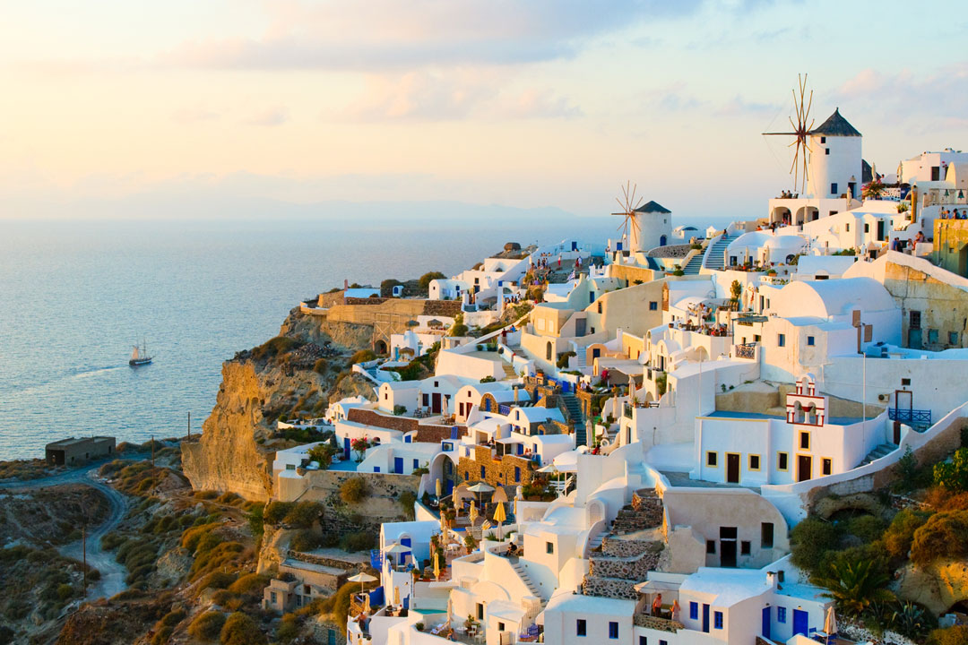 Whitewashed townhouses and windmills atop a cliff in Santorini