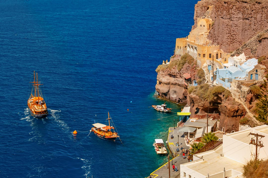 Santorini old port with a traditional wooden ships at sail