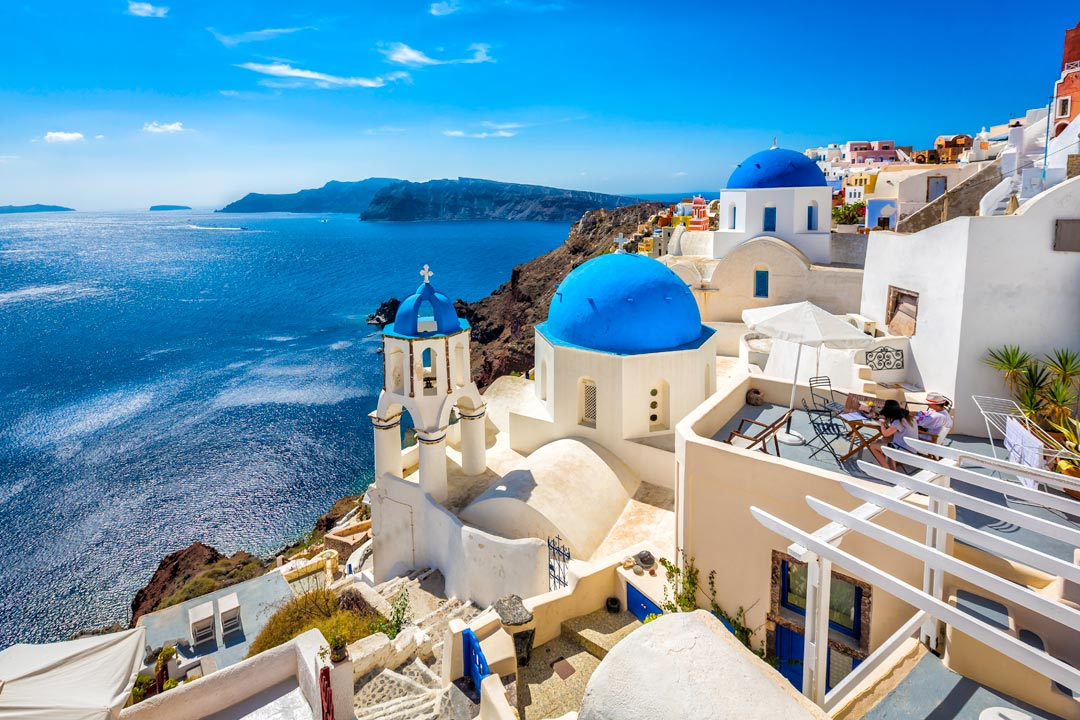 Blue domed church in Santorini with the blue Aegean sea in the background
