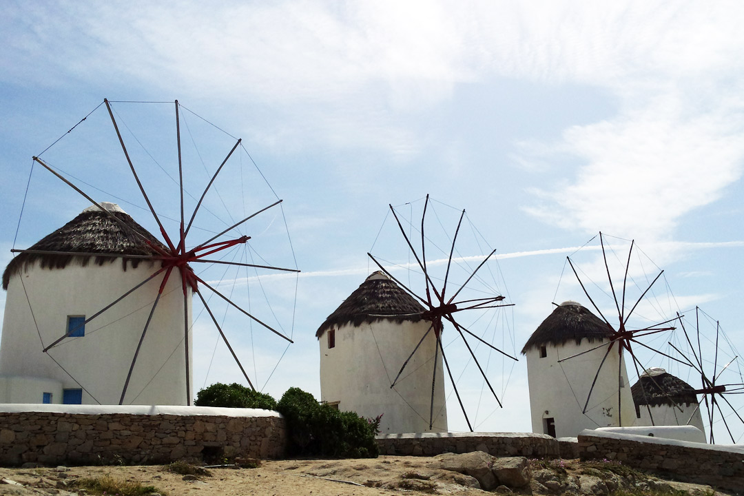 The famous white windmills of Mykonos against a blue sky