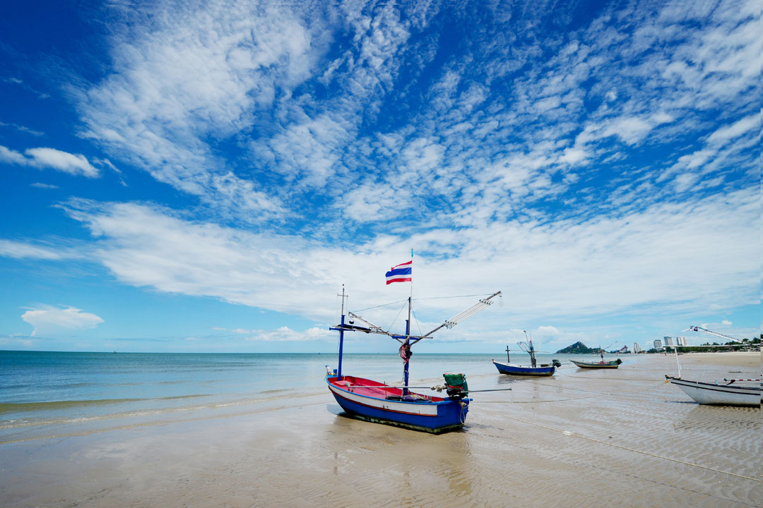 A golden beach with a blue fishing boat sitting in the sand