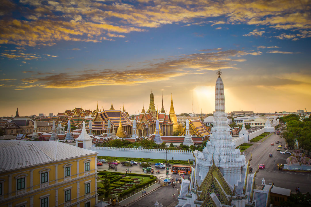 The gold and white stupas and temples of the Grand Palace in Bangkok at sunset