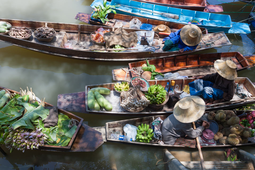 Thai Women in their sturdy canoes laden with tropical fruits at a floating market