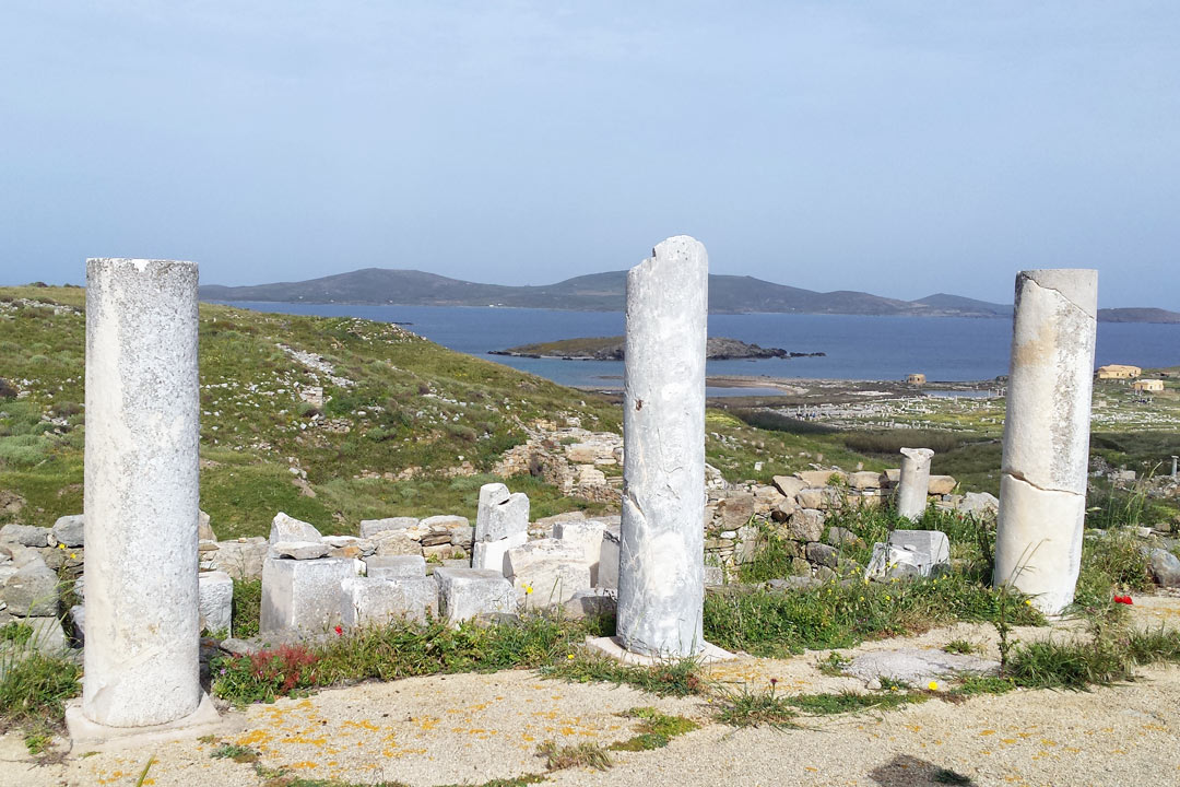 White marble columns of Delos with greenery behind it and the blue Aegean sea