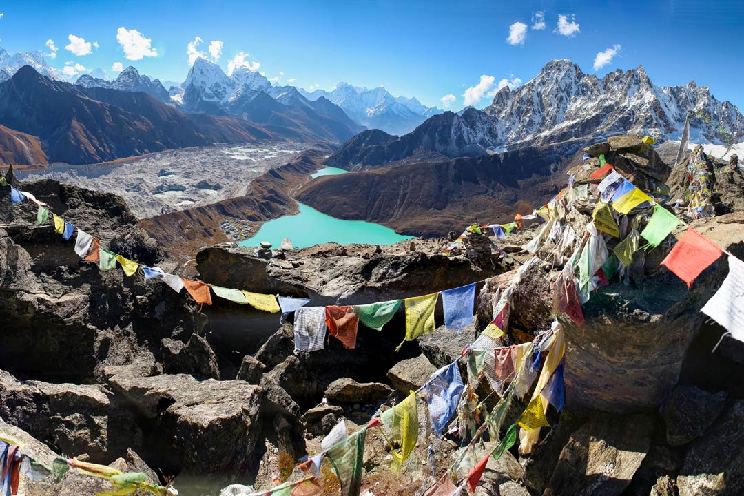 Himalayan Moutnains surround a bright turquoise lake with prayer flags in the foreground