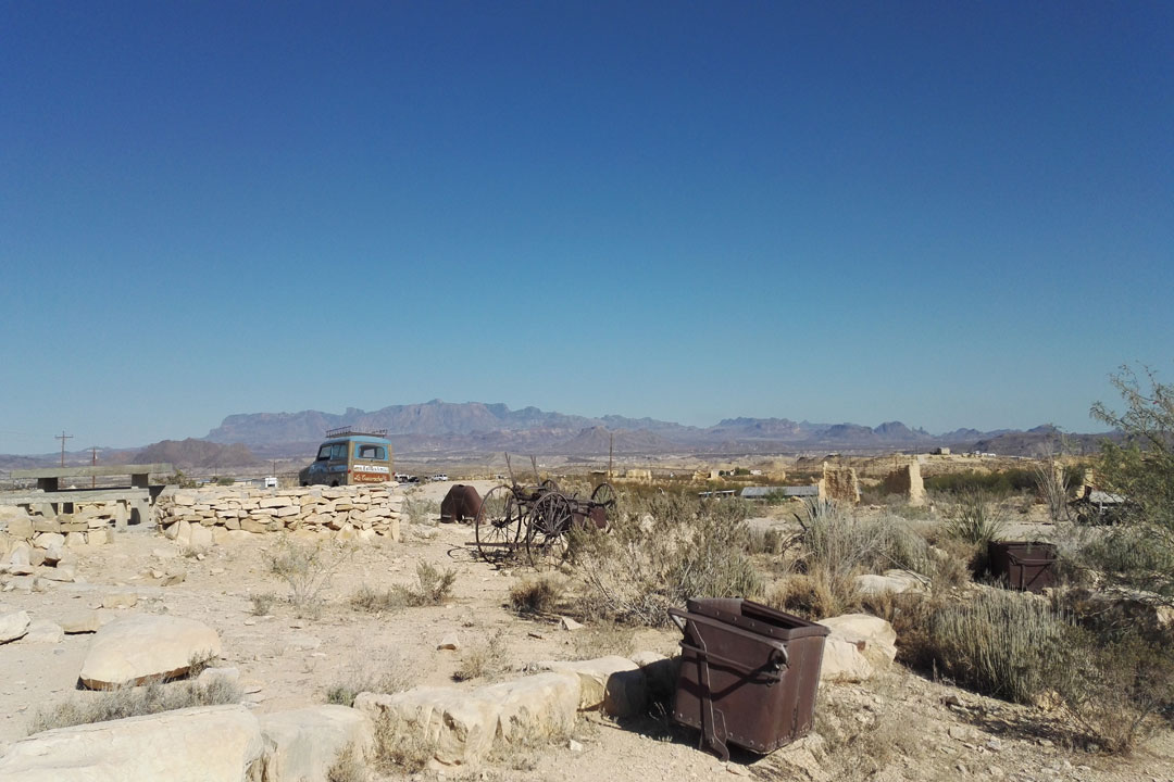 A ghost town showing abandoned mining equipment and cars in a desert