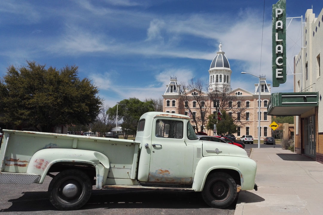 A Texas town with a green vintage car in the foreground and a court building in the background