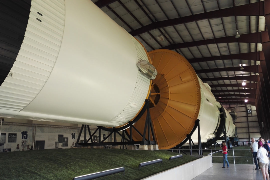 A colossal Saturn V Rocket lieing in a warehouse at Houston Space Centre