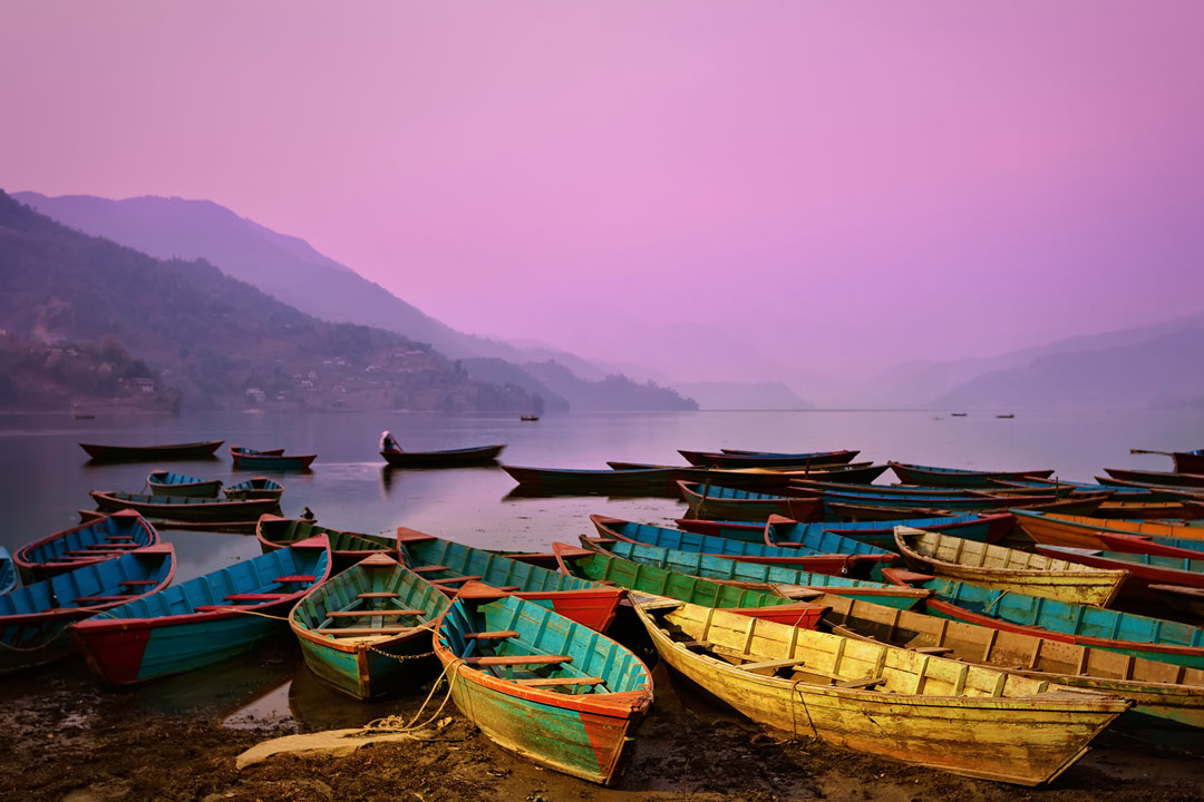 Colourful canoes moored on the lake side with a purple twilight sky in the background
