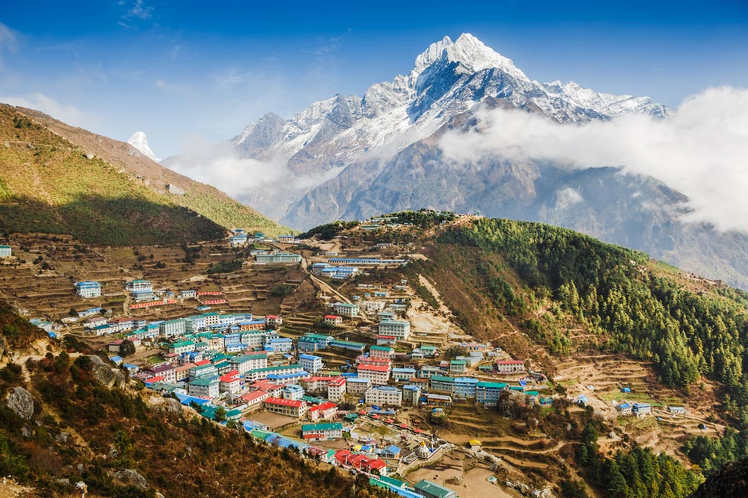 A colourful village clinging to a hillside with the shadow of a colossal snow-capped mountain behind it