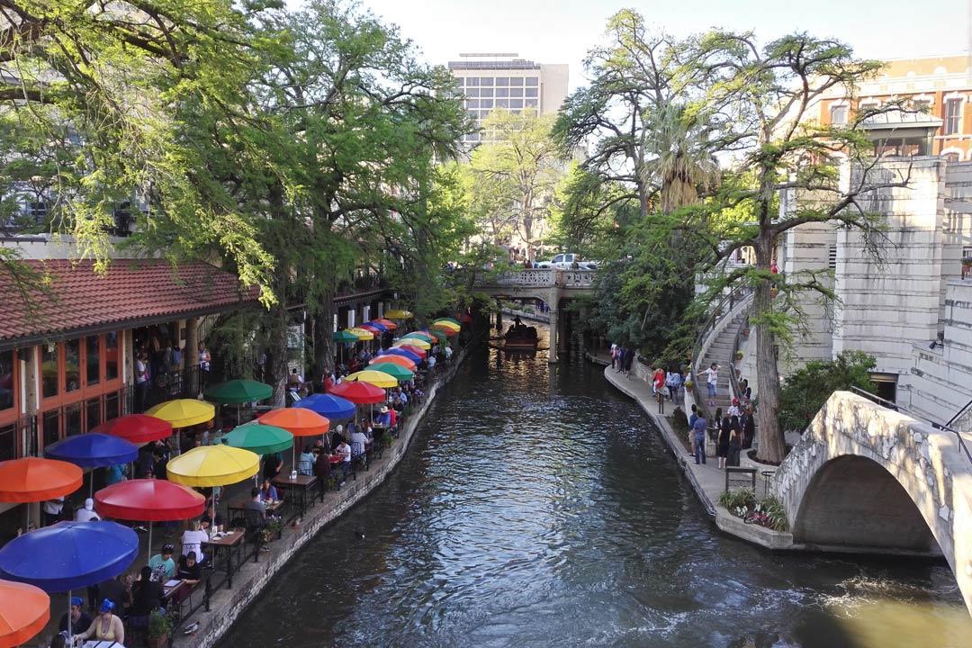 San Antonio Riverwalk showing colourful umbrellas sheltering diners besides a bridge