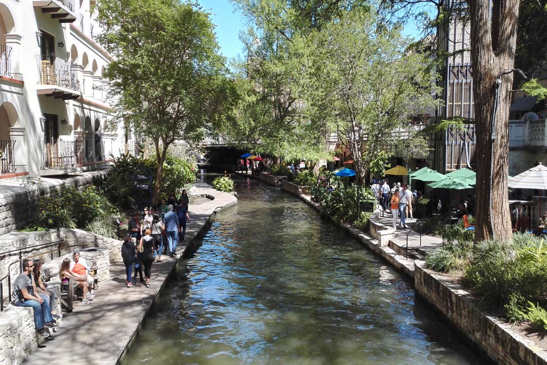 San Antonio riverwalk with people walking on either side