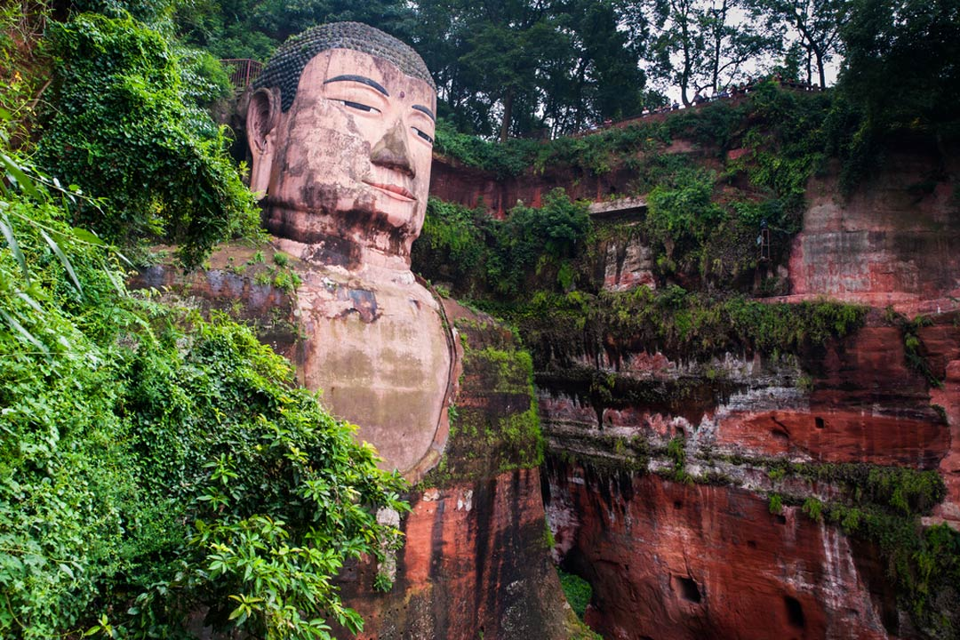 A giant carved buddha hewn out of pink stone with painted facial features surrounded by lush vegetation