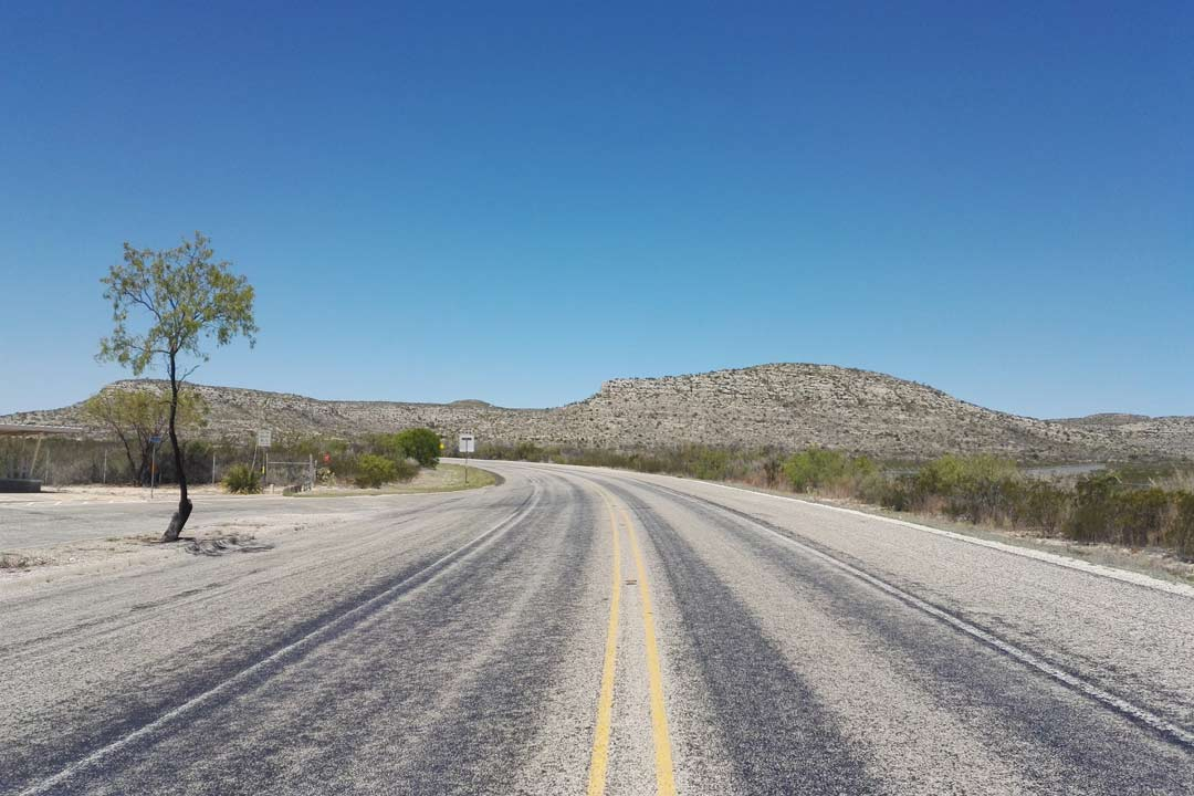 An empty road leading off into the distance of a dusty barren desert