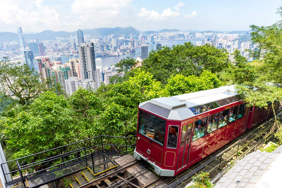 A red fenicula locomotive climbing Victoria Peak overlooking the Hong Kong skyline