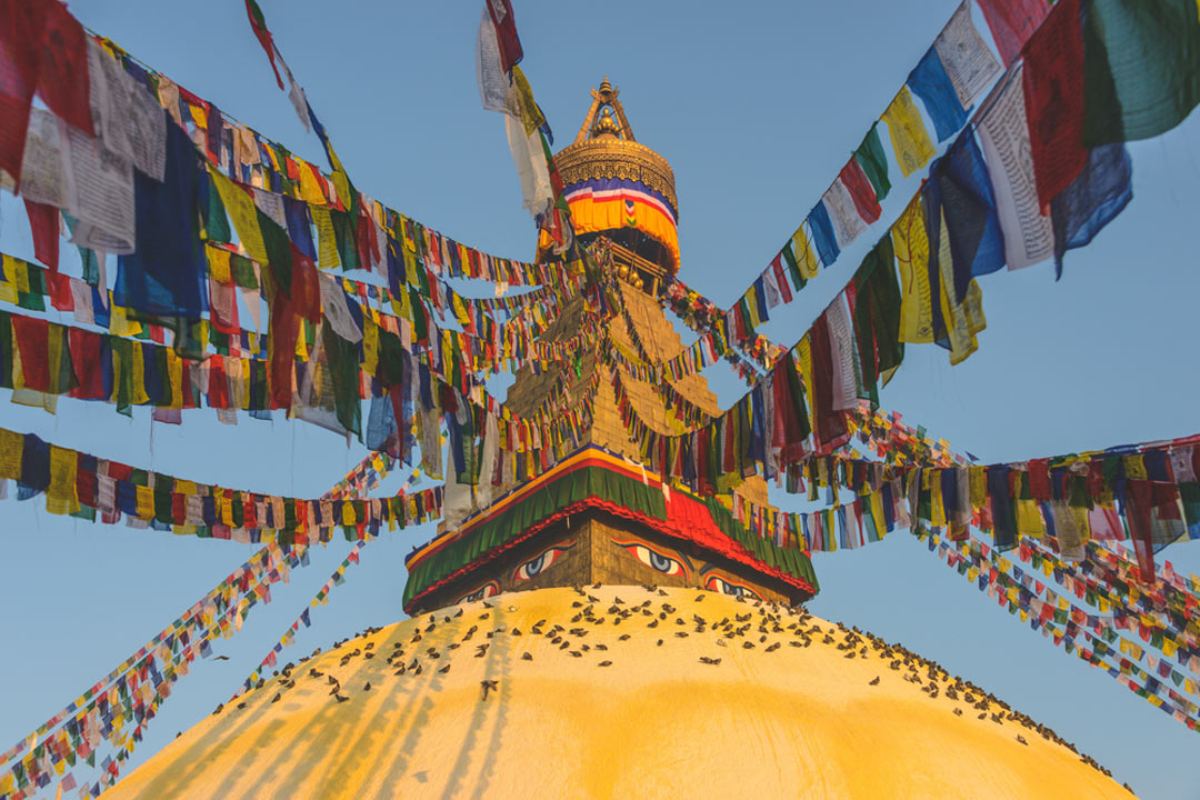 multi-coloured prayer flags hang off a golden stupa with pained eyes on either side