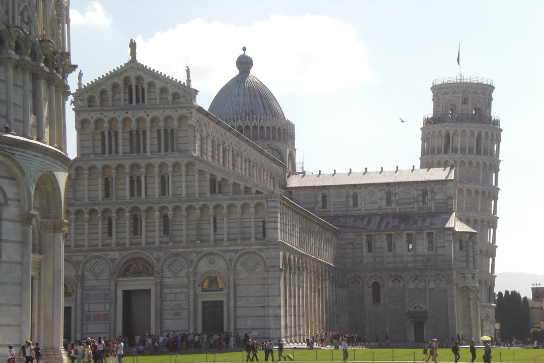 Built on a green field stands Pisa cathedral and its ornamental facade. Decorative pillars lead all the way to the roof of the building. FUrther along a dome towers over the cathedral. In the background stands the leaning tower, jutting out behind the cathedral as it appears to topple over.