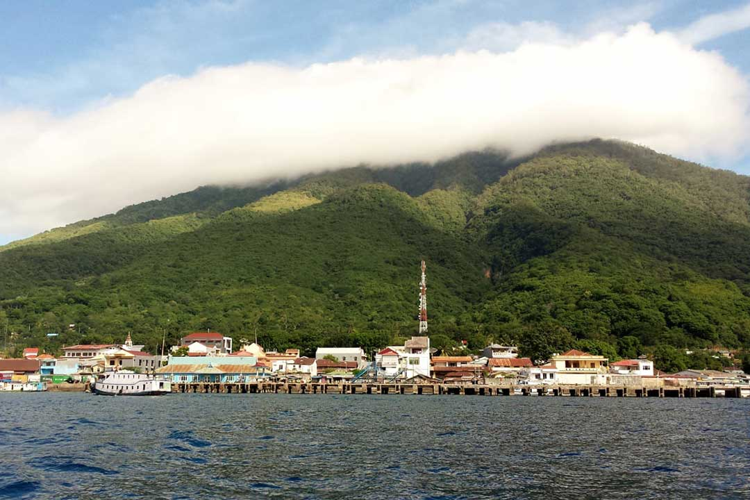 A mountain is covered in lush greenery with its summit shrouded in cloud. In the foreground is the sea and a port town with white buildings and a large pontoon.