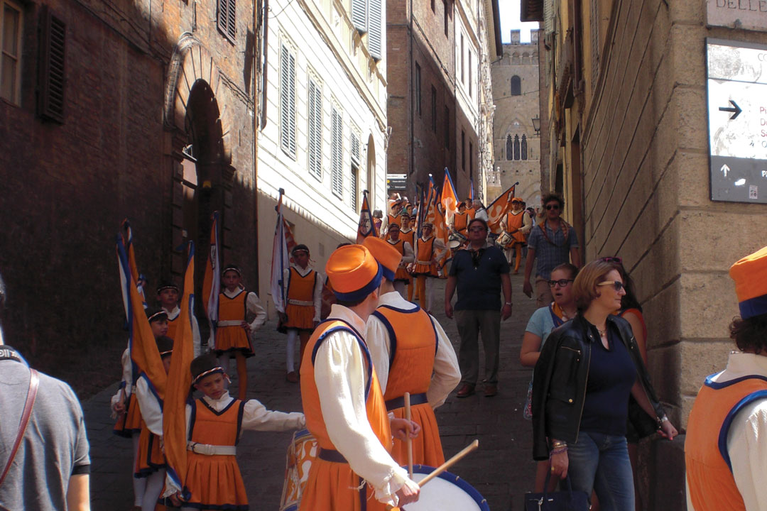 Men and children clad in medieval orange garments are parading through tight Tuscan streets. They are carrying drums and orange flags.