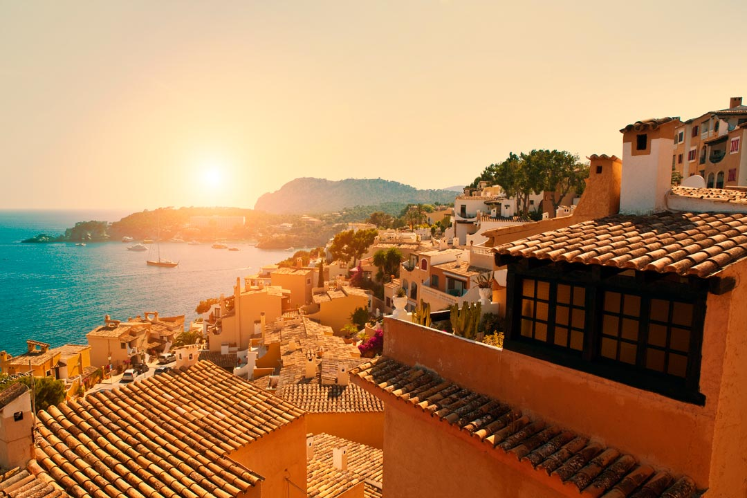 Pastel orange houses with tiled roofs sprawl down a Cliff-side. A bright sun shines down over a cliff in the background with boats sitting in the cove that it protects.