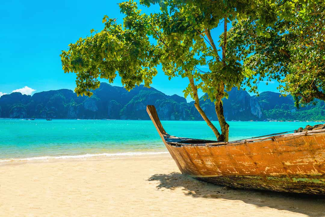 A pure white sandy beach with a small local fishing vessel is beached there with a tree hanging over it. In the background there is a brilliant blue sea and the mountainous terrain of neighbouring islands.